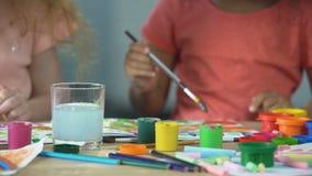 Dwa multiracial dziecka maluje z akwarelami przy warsztatem, twórczość zbiory
