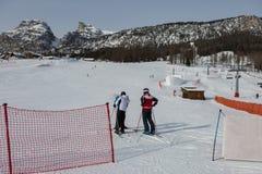 Dwa narciarki z hełmami przygotowywającymi dla narciarstwa obraz stock