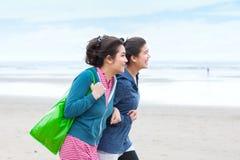 Dwa nastolatek dziewczyny chodzi na plaży na chłodno chmurnym dniu fotografia royalty free
