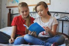 Dwa nastolatek dziewczyny w domu robią pracie domowej zdjęcia royalty free