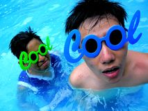 Dwa nastoletniego chłopaka jest ubranym okulary przeciwsłonecznych z słowem cool dla swój ramy w pływackim basenie Fotografia Royalty Free