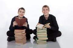 Dwa nastoletniego chłopaka siedzi na podłoga z książkami obrazy stock