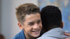 Dwa nastoletniego męskiego przyjaciela wita each inny z uściśnięciem, szkoły średniej przyjaźń zbiory