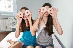 Dwa nastoletniej dziewczyny ma zabawę z donuts fotografia royalty free