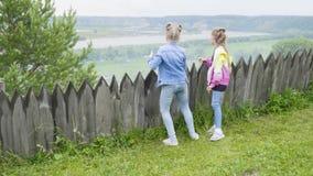 Dwa nastoletniej dziewczyny stoją bezczynnie drewniany płotowy patrzeć w odległość Dziewczyny podziwia lato krajobrazowego las rz zbiory wideo