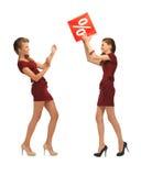 Dwa nastoletniej dziewczyny w czerwonych sukniach z procentu znakiem Zdjęcia Stock