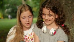 Dwa nastoletniej dziewczyny w lecie w parkowej naturze posiedzenie trawy Trzymają smartphone i sprawdzają fotografie zdjęcie wideo