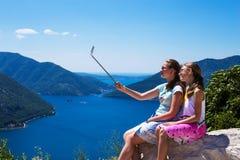 Dwa nastoletniej dziewczyny w robią fotografii na telefonu, selfie kijach i Boko Kotorska góry w Montene i zatoka na tle obrazy royalty free
