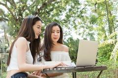 Dwa nastoletniej kobiety spotykają w sklep z kawą use laptopie wpólnie wewnątrz aft Obraz Royalty Free