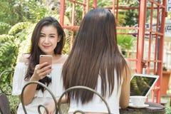 Dwa nastoletniej kobiety spotykają w sklep z kawą use smartphone i laptopie zdjęcie royalty free