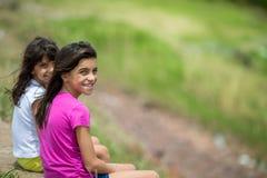 Dwa nastoletniej siostry siedzi outdoors Obrazy Royalty Free