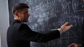 Dwa naukowa pisze na kredowym biurku, dyskutujący matematyk równania i formuły wsiadają zdjęcie wideo