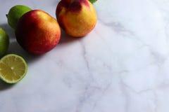 Dwa nektaryny na bielu marmuru powierzchni fotografia stock