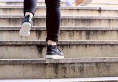 Dwa nogi osoba wspina si? schodki w sneakers zdjęcia stock