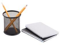 Dwa notepad obok zbiornika z ostrymi ołówkami inside i pojedynczy białe tło zdjęcia stock