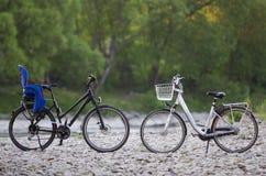 Dwa nowego nowożytnego bicyklu: czerń z błękitnym plastikowym dziecka siedzeniem i biel z koszykową pozycją dalej zaświecaliśmy s Obraz Stock