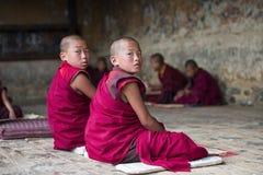 Dwa nowicjusza michaelity Bhutanese młody zwrot patrzeć ciebie ich głowa gdy podczas nauki, Bhutan obraz stock
