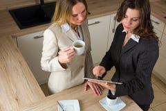 Dwa nowożytnej biznesowej kobiety z pastylką i kawą w kuchni Zdjęcia Royalty Free