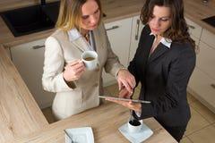 Dwa nowożytnej biznesowej kobiety z pastylką i kawą w kuchni Zdjęcie Stock