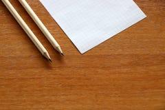 Dwa ołówka i kawałek papieru na drewnianym tle obraz royalty free