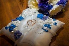 Dwa obrączki ślubnej kłamają na poduszce, bukiet błękita, bielu i purpur kolory, Zdjęcia Royalty Free