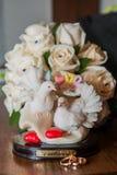 Dwa obrączki ślubnej kłamają stół Figurek gołąbki Miłość Fotografia Royalty Free