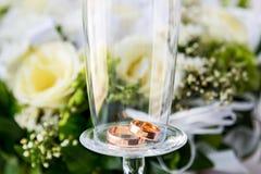 Dwa obrączki ślubnej po środku szkła na tle kwiaty Obrazy Stock