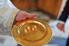 Dwa obrączki ślubnej przy złotym naczyniem gotowym ksiądz na kościół cer obrazy stock