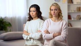Dwa obrażającej kobiety siedzi na kanapie z rękami krzyżowali między przyjaciółmi, konflikt obrazy stock