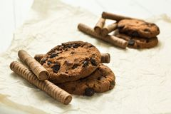 Dwa obruszenia czekoladowe gofr rolki, ciastka na drewnianym bielu stole zdjęcie stock