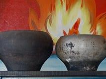 Dwa obsady stary żelazo puszkuje na tle płomień Nieociosana kuchnia, gospodarstw domowych naczynia zdjęcie stock