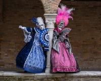Dwa odwiedzającego jest ubranym jaskrawy barwiących kostiumy i maski przy Wenecja karnawałem Zdjęcie Royalty Free