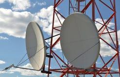 Dwa ogromnej anteny satelitarnej, wspinającej się na telewizi wierza Fotografia Royalty Free