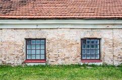 Dwa okno na starej ścianie z gazonem i dachem obrazy royalty free