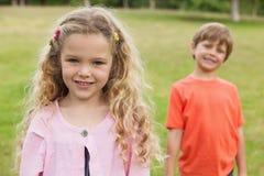Dwa one uśmiechają się dzieciaka stoi przy parkiem Fotografia Stock