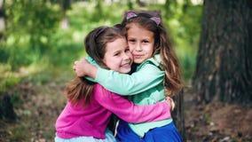 Dwa ono uśmiecha się, śliczne młode dziewczyny ściskają each inny ściśle zbiory