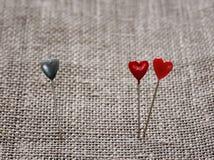 Dwa ostrej szpilki w postaci czerwonych serc zbliżają i jeden błękit wtykający Zdjęcie Stock
