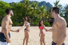 Dwa para Na Plażowym wakacje, młodzi ludzie W miłości Chodzi, mężczyzna kobiety mienia ręk oceanu Denny kurort Obraz Royalty Free
