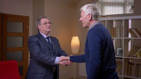 Dwa partnerów biznesowych starszy stojak do trząść ręki jest szczęśliwy podpisywać kontrakt w biurze zdjęcie wideo