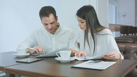 Dwa partnera biznesowego dyskutuje pracę i ono uśmiecha się podczas gdy siedzący w kawiarni fotografia stock