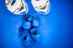 Dwa pary błękitne walczące rękawiczki i dwa białego hełma z jasnym klingerytem dziurkowali maski na błękitnej podłodze Karate wyp zdjęcia royalty free