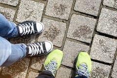 Dwa pary działającego buta i kapcia obuwiana pozycja wpólnie na popielatym ceglanym przejściu Obraz Royalty Free