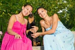 Dwa piękna młoda kobieta bawić się z szczeniakiem w parku Zdjęcie Stock