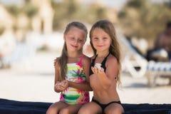 Dwa piękna szczęśliwa dziewczyna na plaży blisko morza z skorupami w ich rękach zdjęcie royalty free