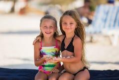 Dwa piękna szczęśliwa dziewczyna z skorupami w ich rękach zdjęcia stock