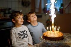 Dwa pięknego dzieciaka, małych preschool chłopiec świętuje, urodziny i podmuchowe świeczki na domowej roboty piec torcie, salowym zdjęcia stock