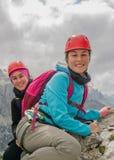 Dwa pięknego młodego żeńskiego halnego arywisty ono uśmiecha się behind i góra krajobraz obraz stock