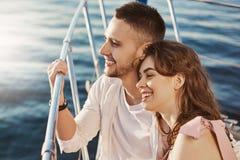 Dwa pięknego zamężnego ludzie w miłości, ono uśmiecha się szeroko podczas gdy siedzący przy łękiem łódź i trzymający poręcz Para  obrazy stock