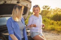 Dwa pięknej blondynki dziewczyny dyskutuje samochodowe naprawy na wiejskiej drodze mają zabawę w promieniach obrazy stock