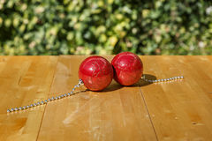 Dwa pięknej czerwonej Bożenarodzeniowej piłki na stole Obrazy Stock
